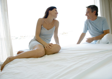 Mature couple sitting on bed, smiling at each other