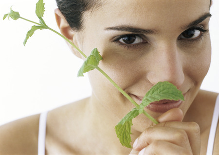 holistic view: Woman holding sprig of mint to nose, smiling at camera, close-up