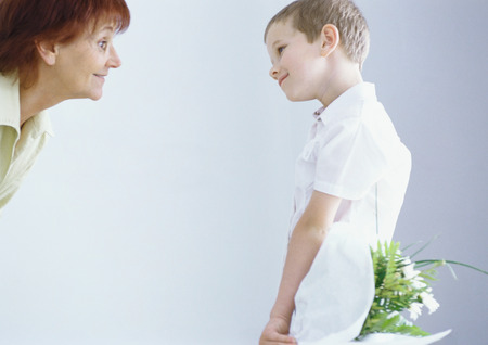 Boy surprising grandmother with bouquet of flowers