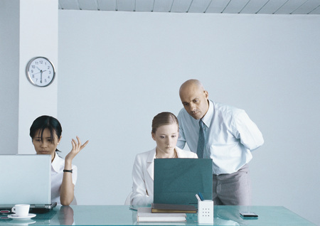 Two professional women working on laptops, boss looking over one womans shoulder LANG_EVOIMAGES