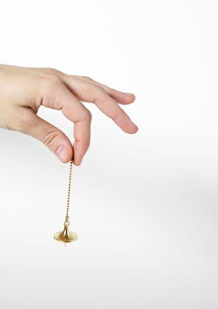 Hand holding pendulum LANG_EVOIMAGES