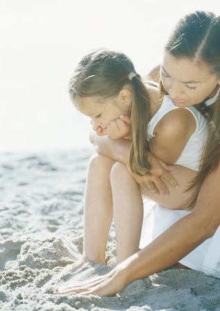Girl sitting on mothers lap on beach