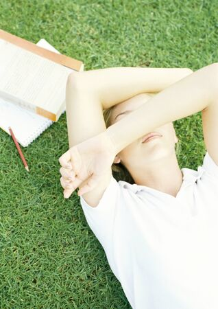 Female student lying on grass with arms over eyes