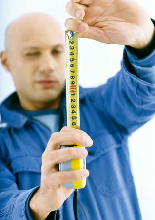 Man holding out measuring tape