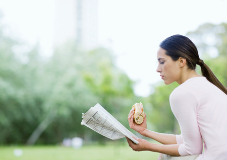 Young woman reading newspaper and holding sandwich in urban park LANG_EVOIMAGES
