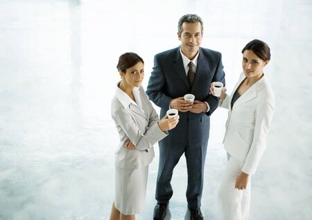 Three executives standing together with cups of coffee