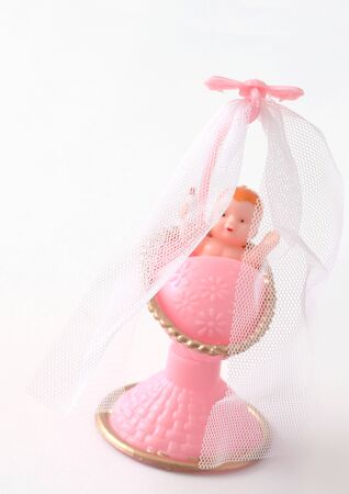 Plastic baby in pink crib