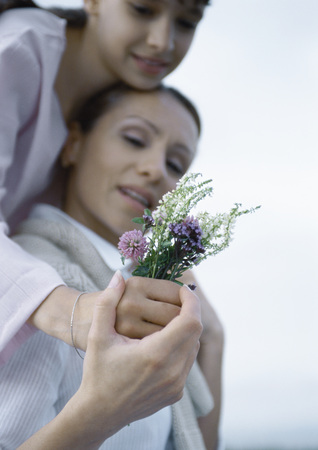 Girl embracing mother from behind, mothers hand over girls, holding bouquet of wildflowers