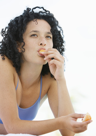 clementines: Young woman eating orange LANG_EVOIMAGES