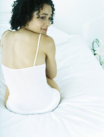 Woman sitting on bed wearing underclothes, looking over shoulder, rear view
