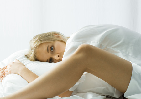Young woman in bed, bending forward