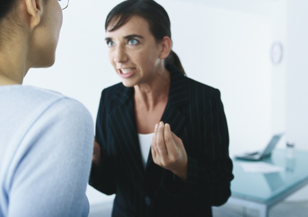 Businesswoman speaking and gesturing angrily to second woman