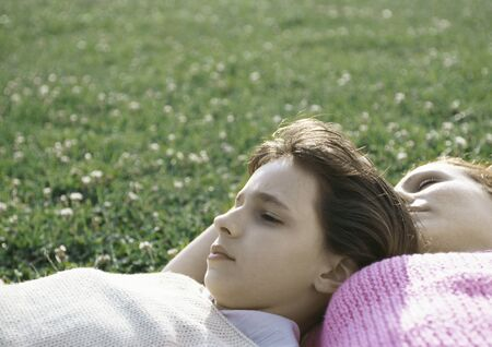 Girl and mother lying on grass LANG_EVOIMAGES