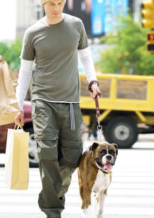 Young man carrying shopping bag and walking dog