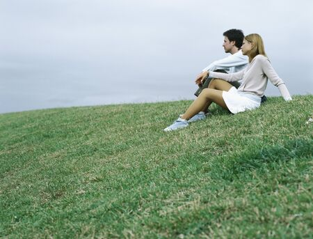 repose: Couple sitting on grass looking into distance