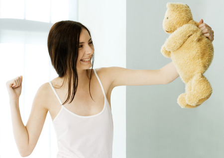 Young woman holding up teddy bear and making fist