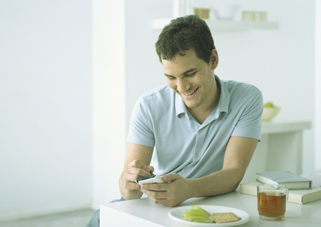 Young man sitting at table with food, working on electronic organizer