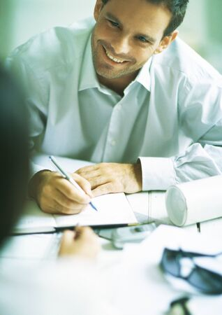 Man smiling while writing in agenda, looking at second person