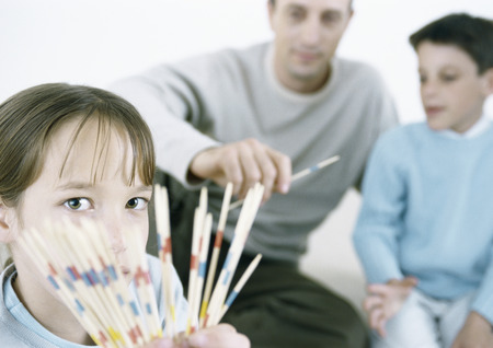 Girl holding out pick up sticks, father and boy in background