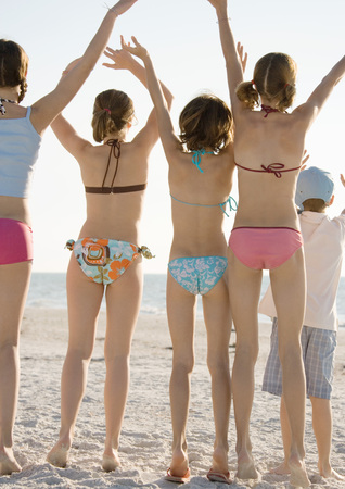 Group of kids waving on beach, rear view LANG_EVOIMAGES