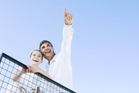 chainlink fence: Man standing outdoors with daughter, pointing at the sky, both looking up and smiling, low angle view