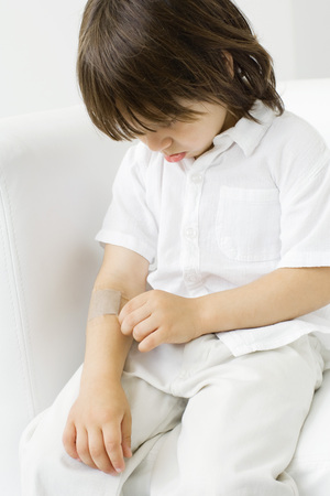 Little boy picking at adhesive bandage on his arm, head down