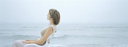 Mujer sentada en la silla, escuchando auriculares, mar en el fondo