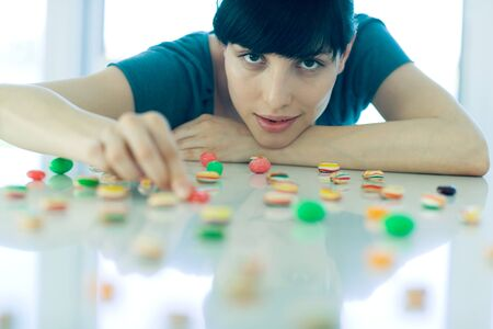Woman arranging pieces of candy on table