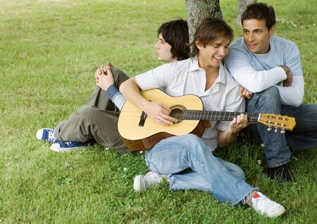 Young male friends sitting near tree, playing guitar
