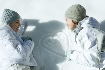 Two teen girls lying on snow, looking at heart with initials traced in snow