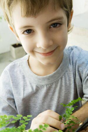 Boy touching plant, smiling at camera, close-up