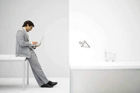 Businessman sitting on desk, shopping online, shopping cart and cursor in foreground