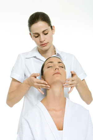 holistic view: Massage therapist giving neck massage to woman with her head back and eyes closed