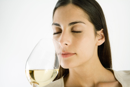 Woman smelling glass of white wine, eyes closed LANG_EVOIMAGES
