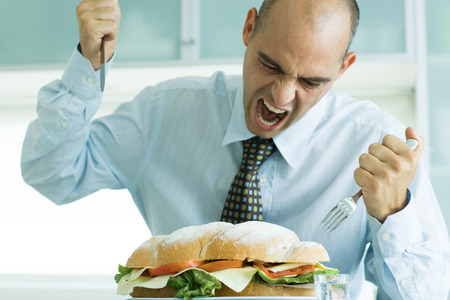 Man yelling and attacking large sandwich with knife and fork