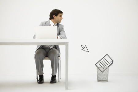 Businessman sitting at desk, looking at computer cursor pointing to document in trash can LANG_EVOIMAGES
