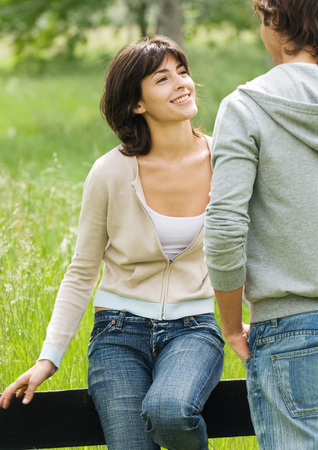 Young woman sitting on a wooden fence looking at young man LANG_EVOIMAGES