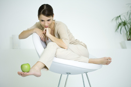 Woman sitting in chair, balancing apple on foot