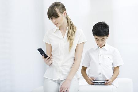 jugando videojuegos: Young woman looking at cell phone while boy plays handheld video game