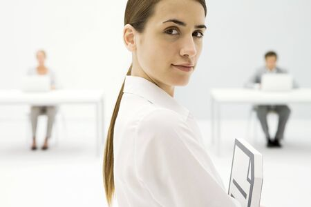 Businesswoman smiling over shoulder at camera, employees working in background LANG_EVOIMAGES