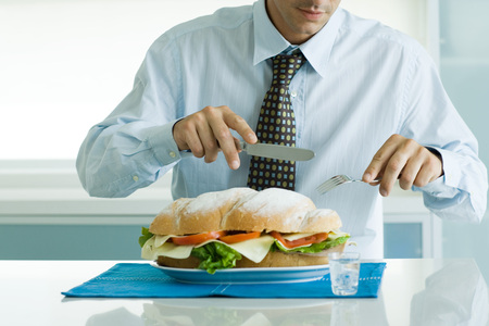 Man eating large sandwich with knife and fork