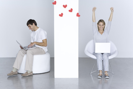 partitions: Man and woman using laptop computers, hearts floating between them, womans arms raised