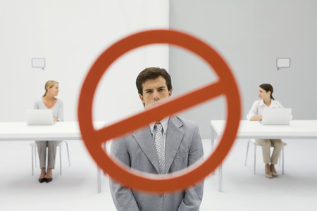 Warning sign across businessman in office, two women sitting with laptops in background LANG_EVOIMAGES