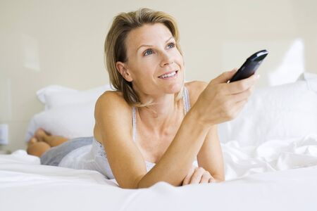 Woman lying on stomach in bed, holding remote control, looking up
