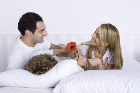 Family lying in bed together, father and son giving mother a flower LANG_EVOIMAGES