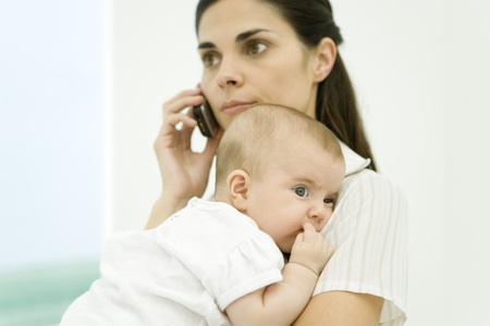 Mother holding infant, using cell phone LANG_EVOIMAGES