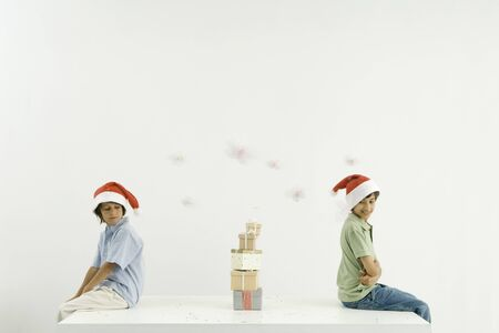 Two brothers sitting back to back, Christmas gifts stacked between them, both wearing Santa hats