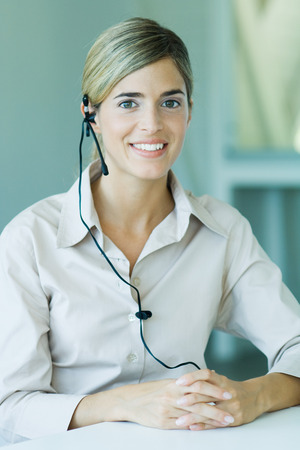 Young businesswoman wearing headset, smiling at camera, waist up