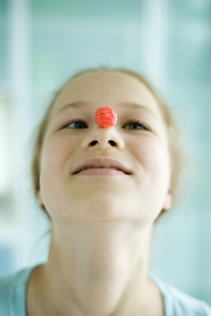 Girl balancing piece of sugary cereal on nose