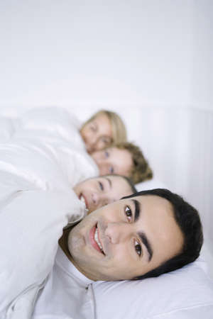 Man lying in bed with his family, smiling at camera